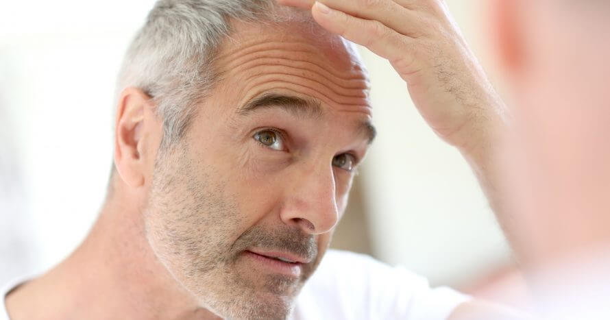 Mature man in bathroom taking care hair